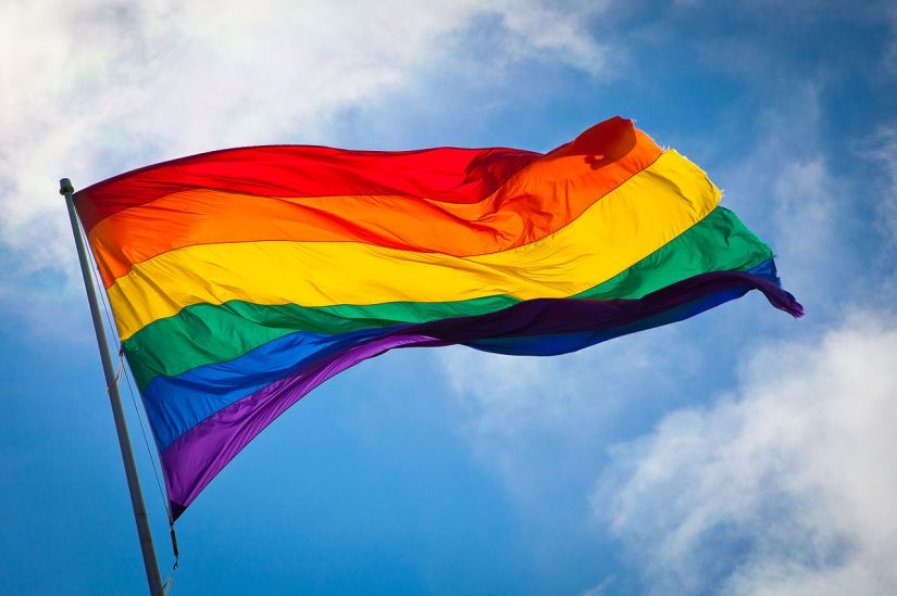 rainbow flag blowing in wind against cloudy blue sky background